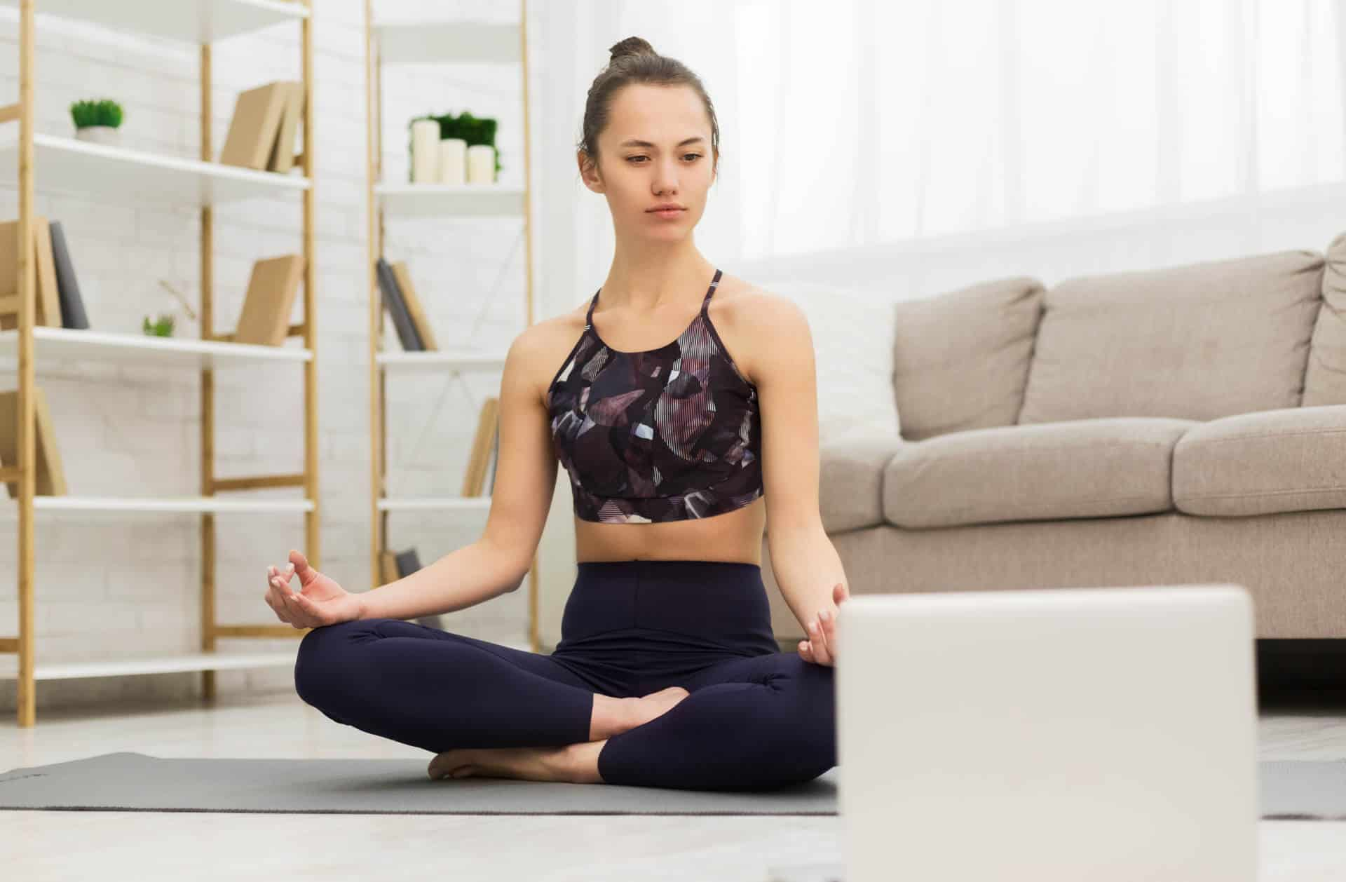 Online training. Girl sitting in lotus position with laptop, watching lesson at home